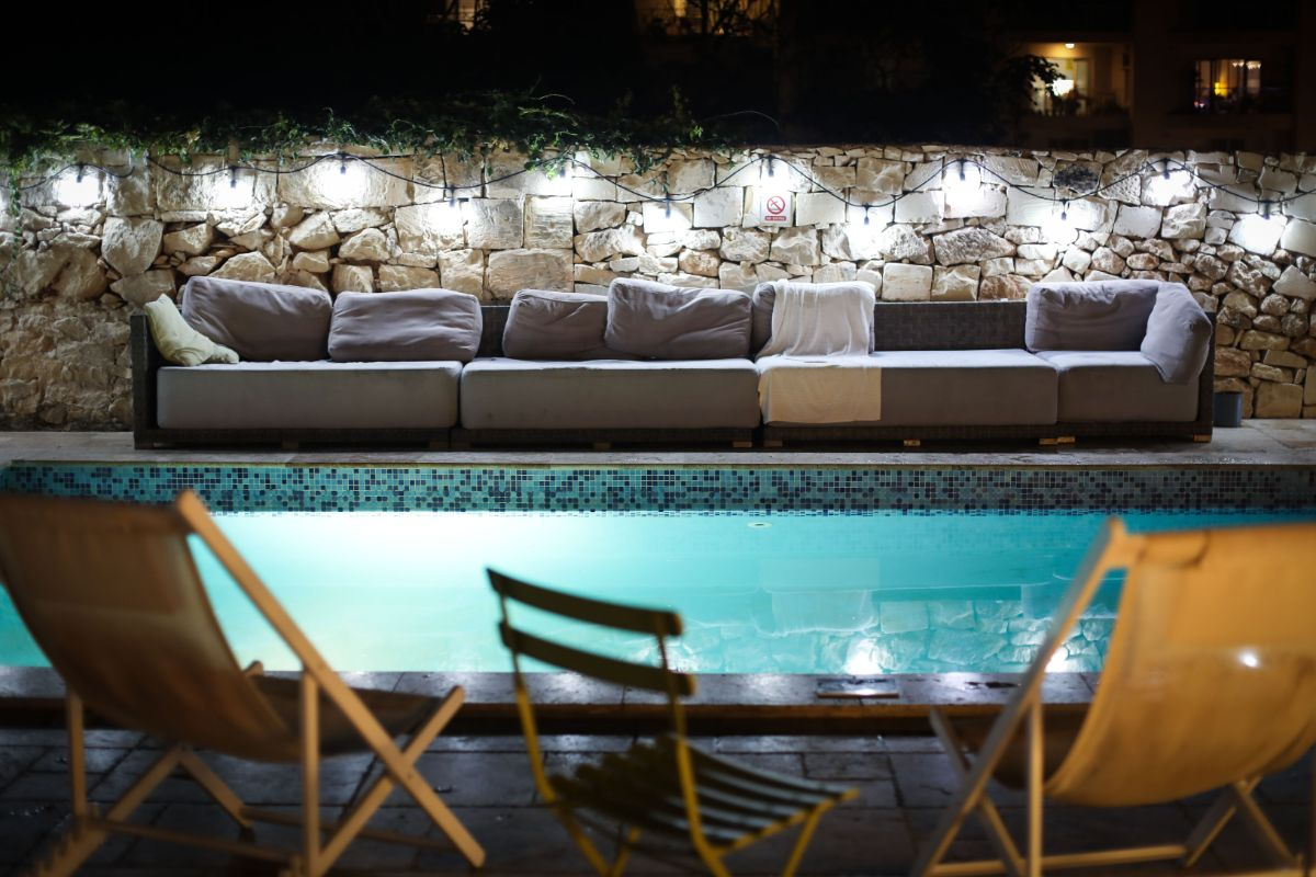 Night-time Patio pool side with stone wall