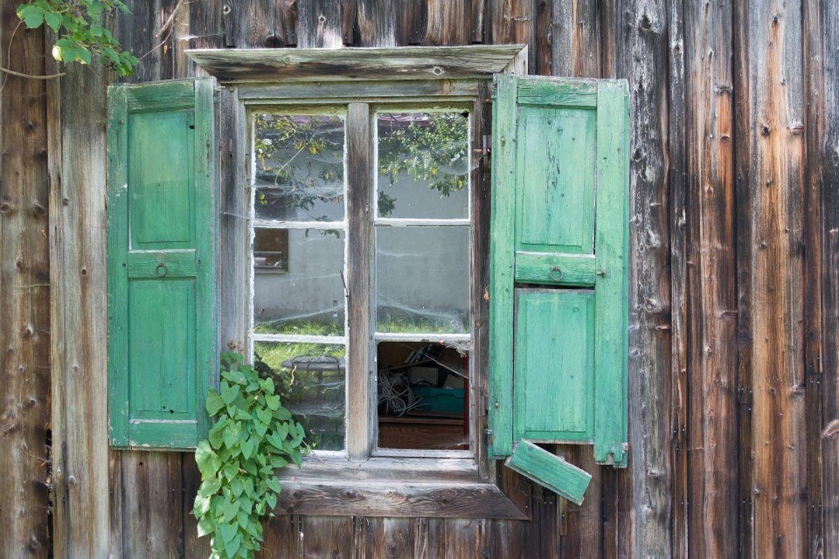 broken shutters of log cottage