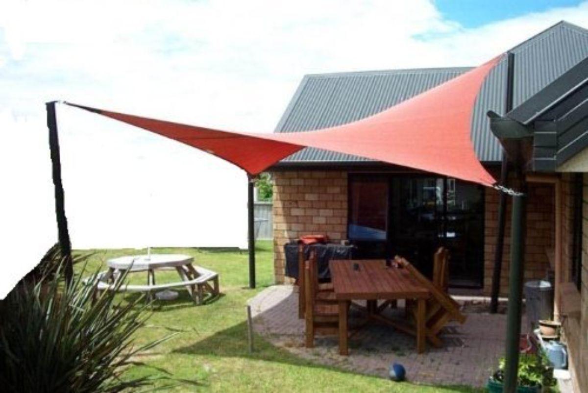 Terracotta sun sail shade outside log cabin